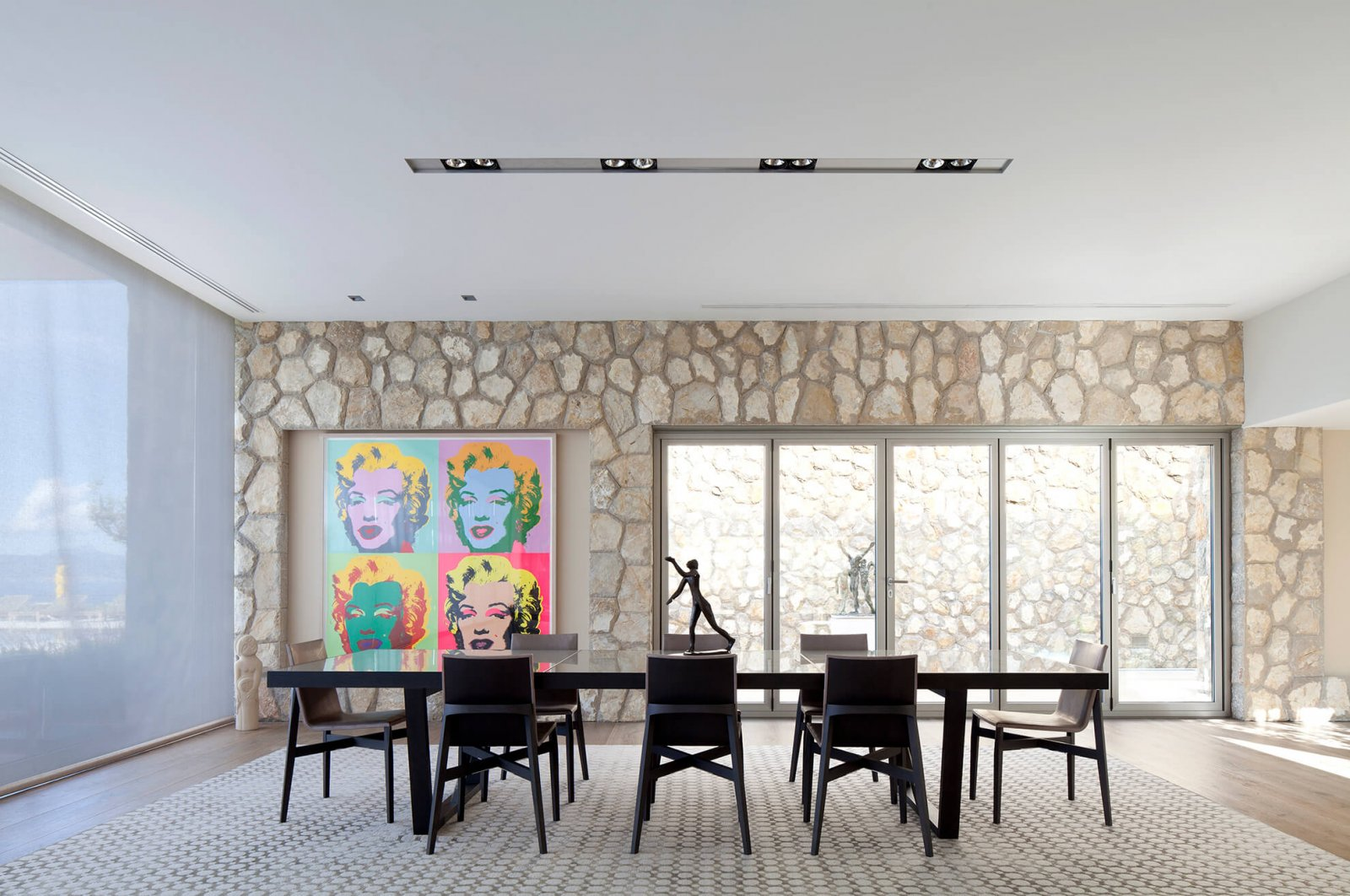 Another detail view of the large dining room table, in front of the sliding glass doors that lead a side garden entrance