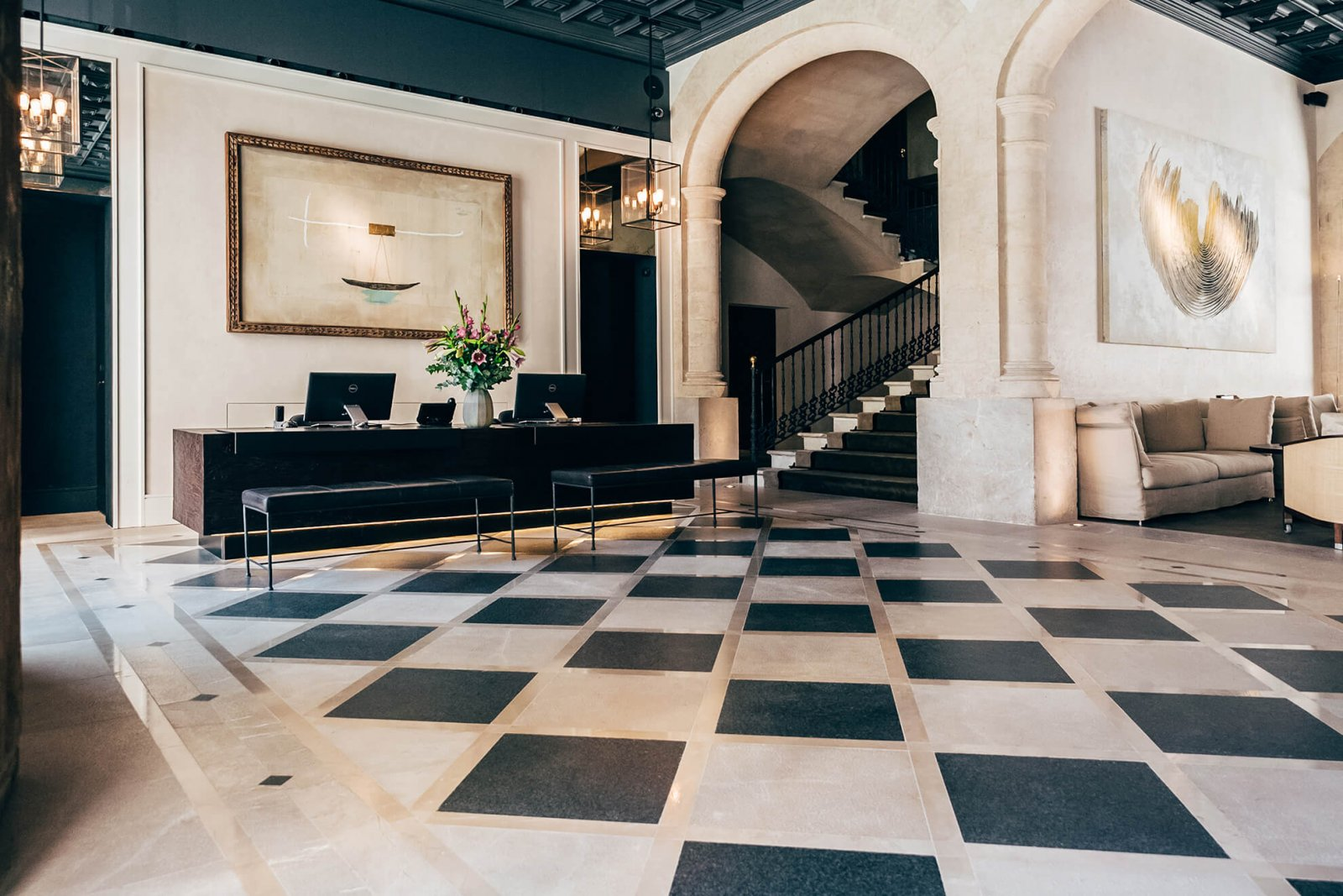 Detail of the hall with the front desk and majestic stairs at Sant Francesc Hotel Boutique