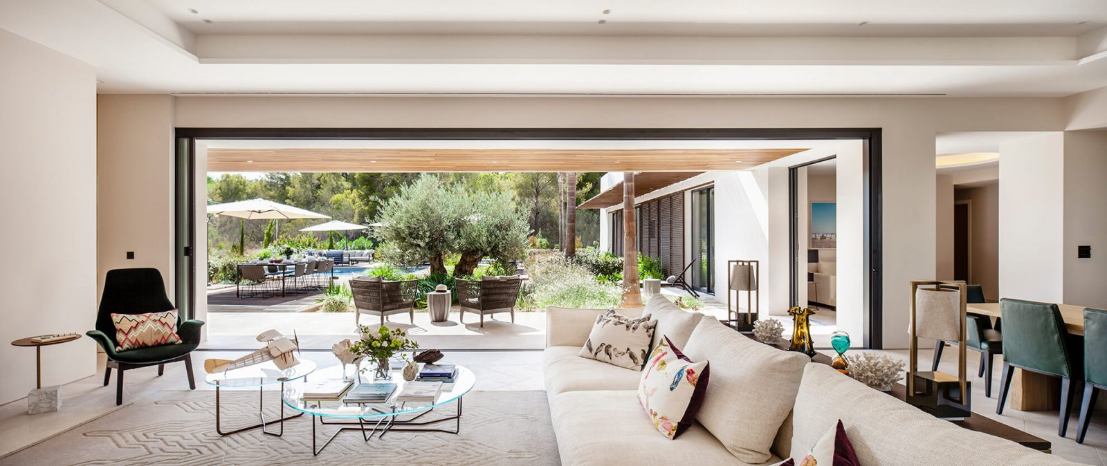 Another view of the living room joined through a large open sliding glass door to the chill-out, garden, and swimming pool, surrounded by trees of the Sol de Mallorca house