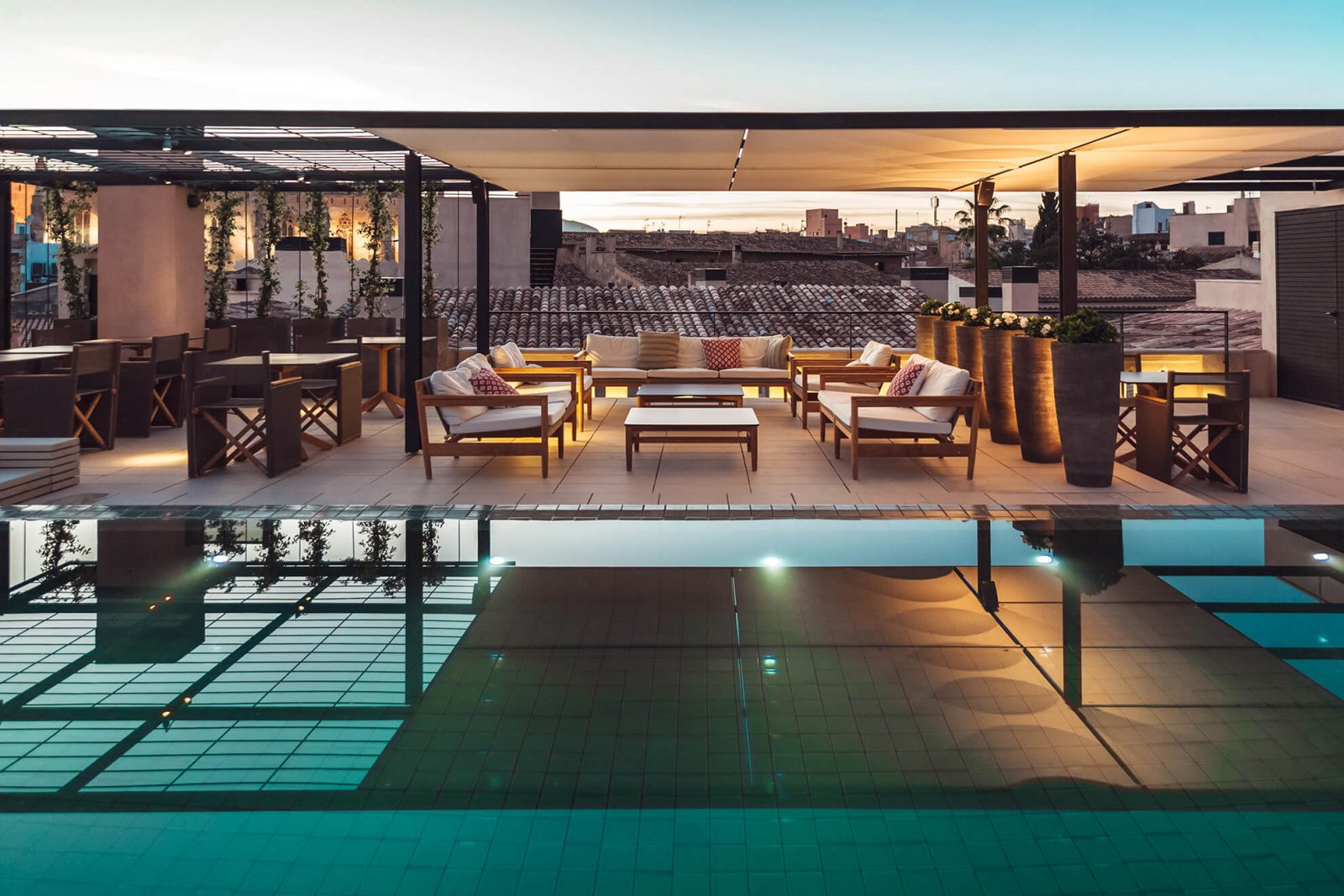 Detail view of the pool and covered chillout area at the Sant Francesc Hotel boutique during sunset with views of the city