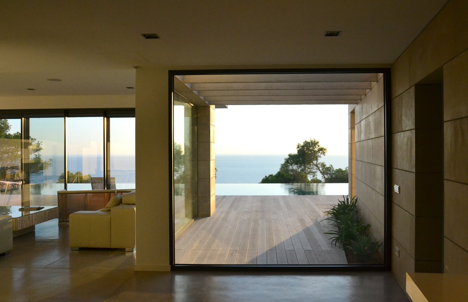 Interior view of the house with large windows, infinity pool and the sea in the background
