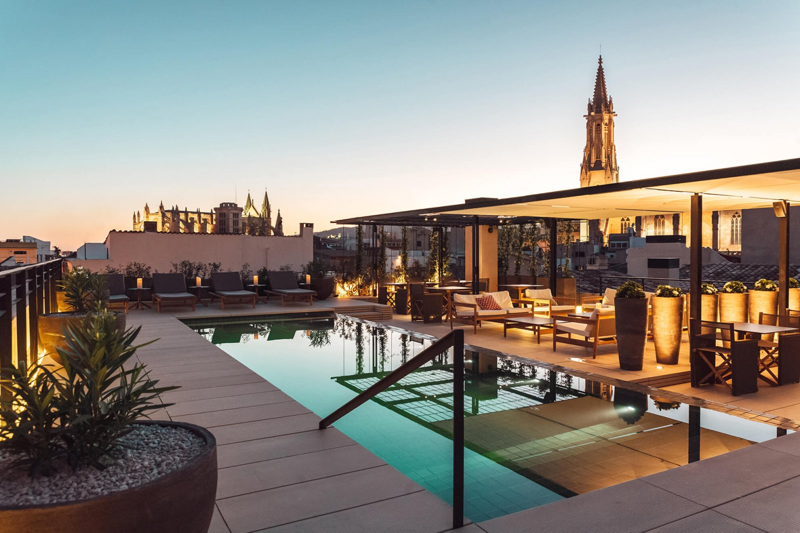 View of the upper terrace with chill out area, pool and views of the city at Sant Francesc Hotel Boutique during sunset