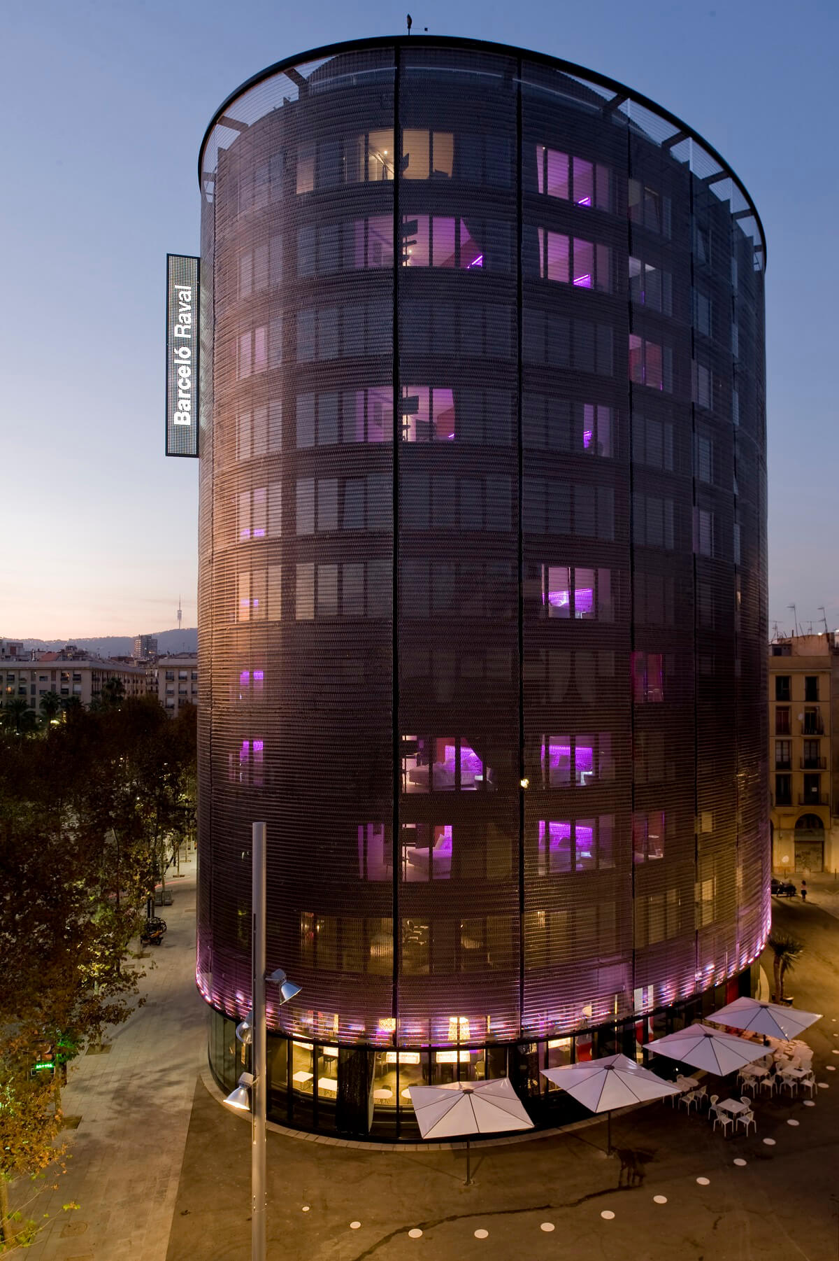 Exterior view of the oval hotel raval tower with details inside the lilac rooms at night