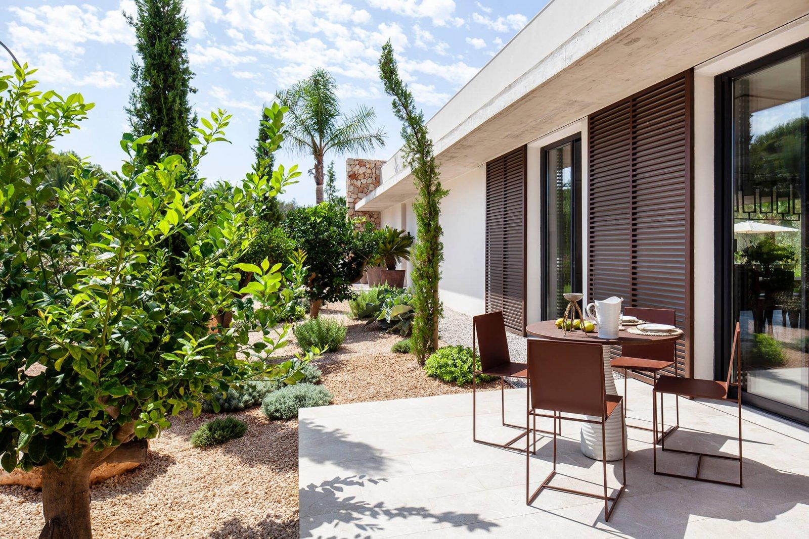 Detail view of the garden with trees, table area and interior facade of the Casa del Sol de Mallorca