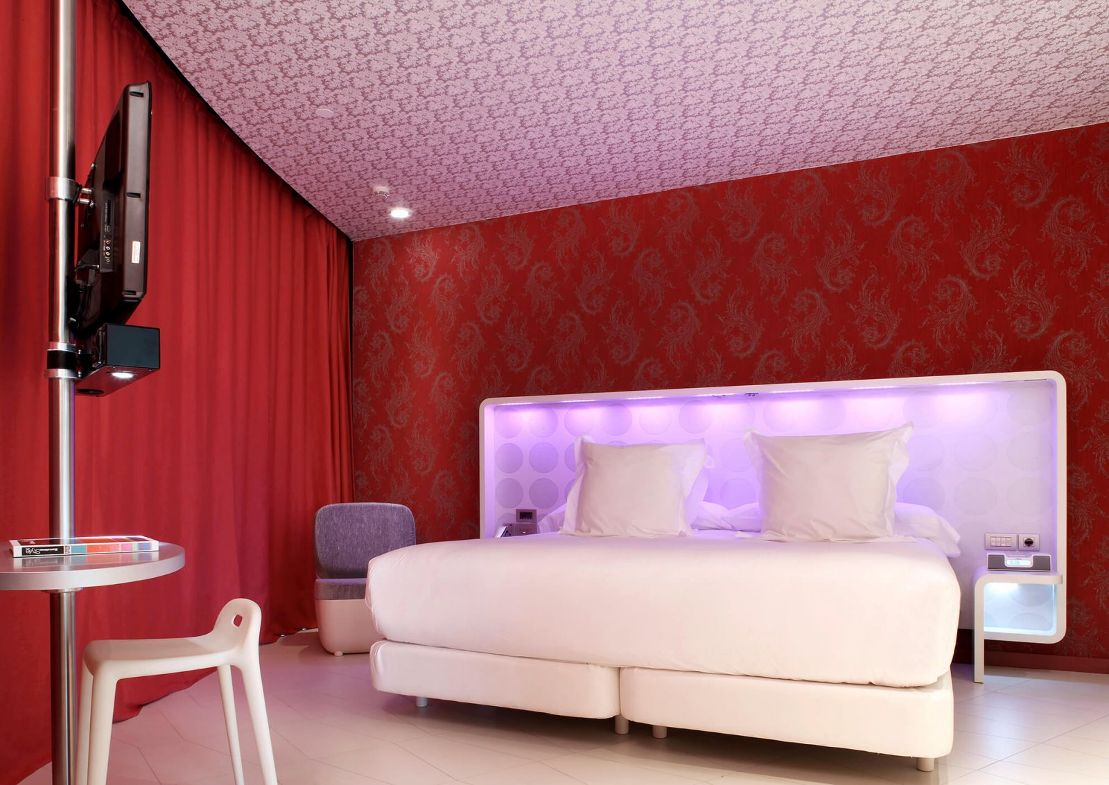 View of another room with double bed, red walls, lilac lights' headboard and patterned ceiling of the hotel raval