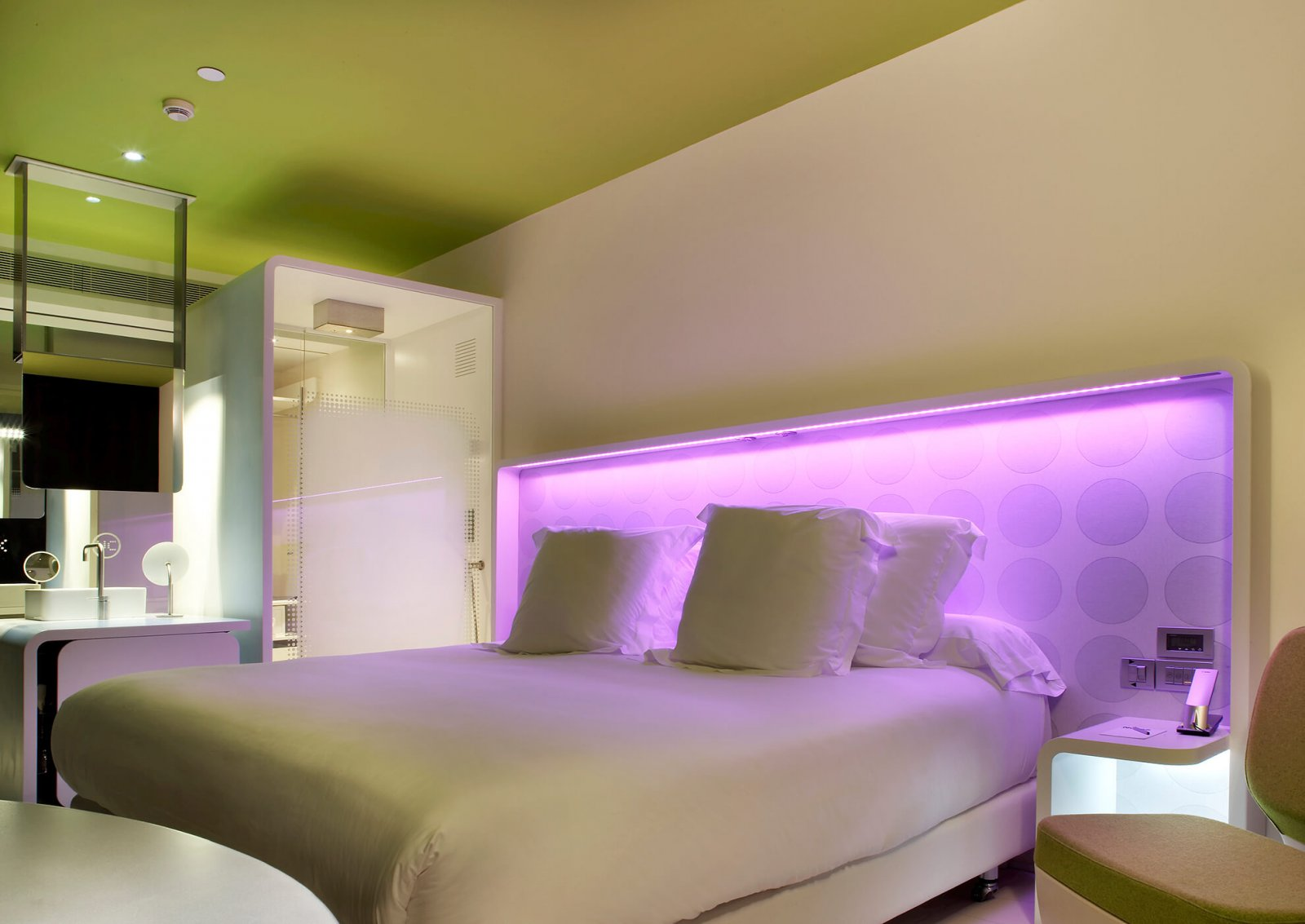 View of a bedroom with double bed and lilac lights' headboard, bathroom and dressing and sink of the hotel raval