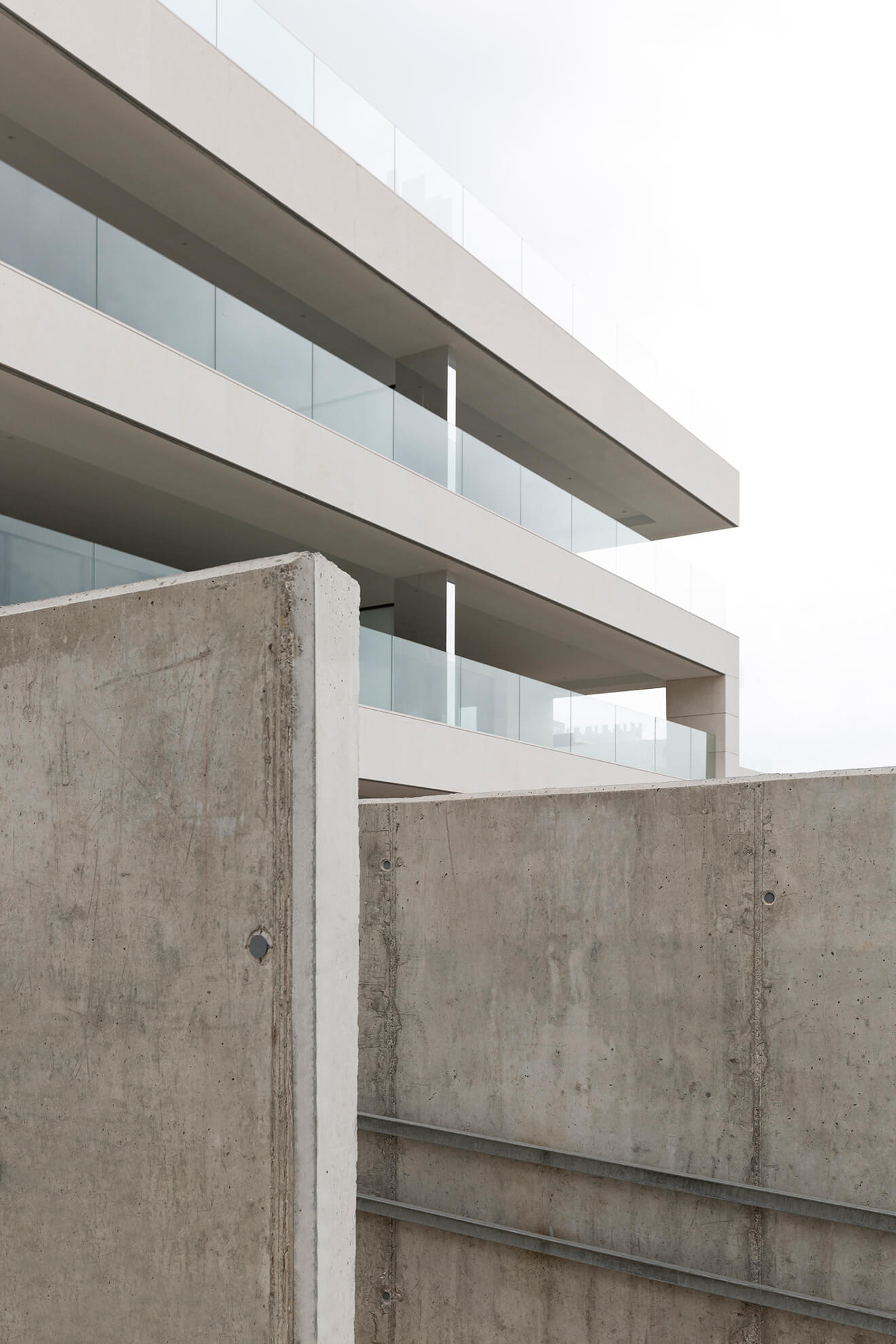 Detail of one of the concrete walls of a common area, and behind, one of the buildings of the Talamanca residential II