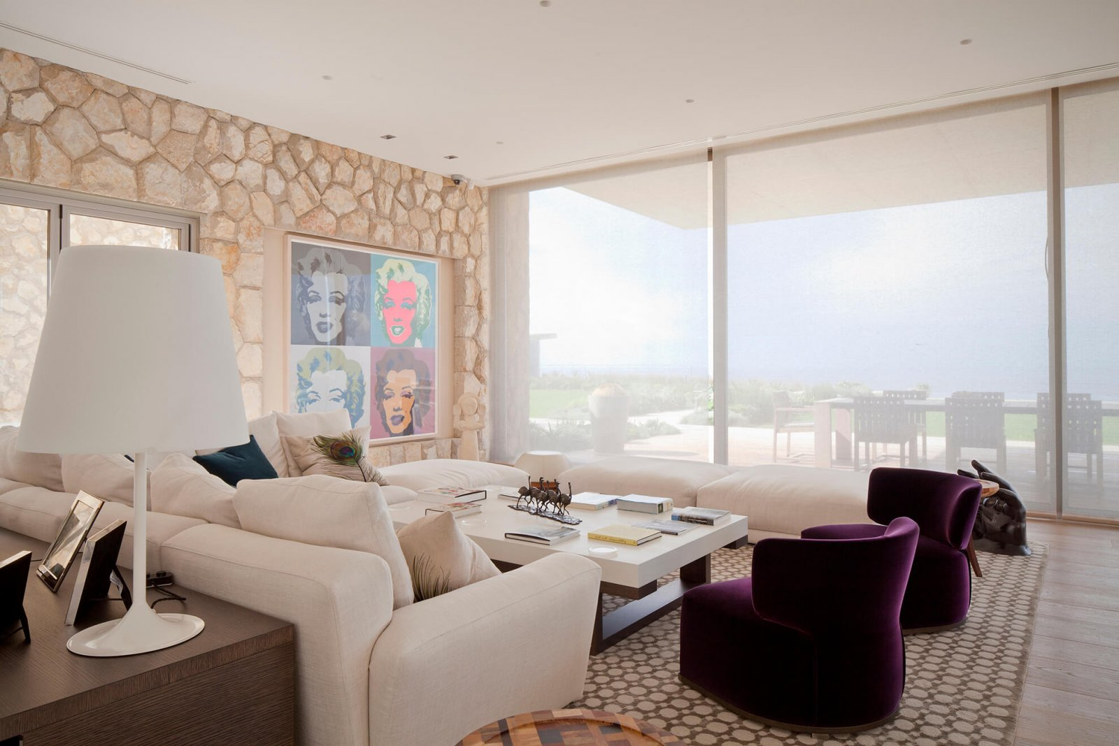 Detail view of the living room with stone wall and light sofas, in front of the sliding glass doors that lead to the garden