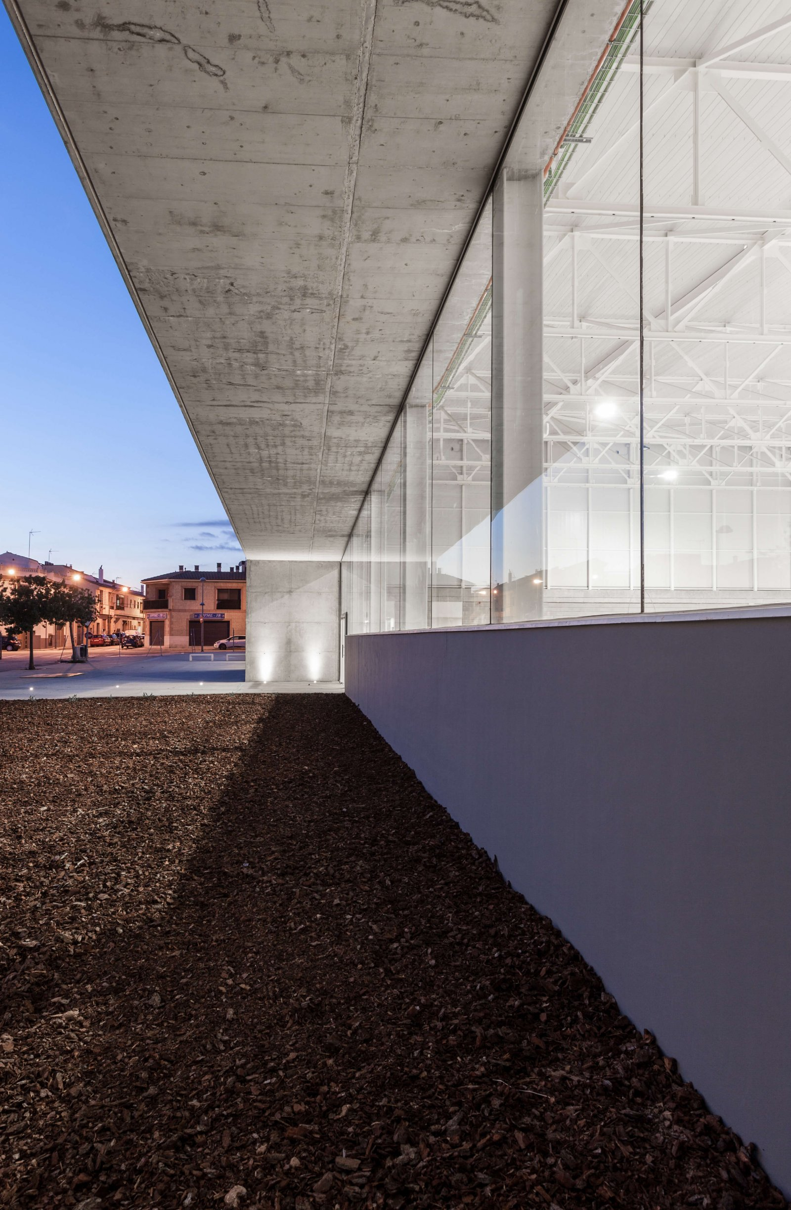 Close up view of glass walls, concrete exterior ceiling and white industrial style interior ceiling