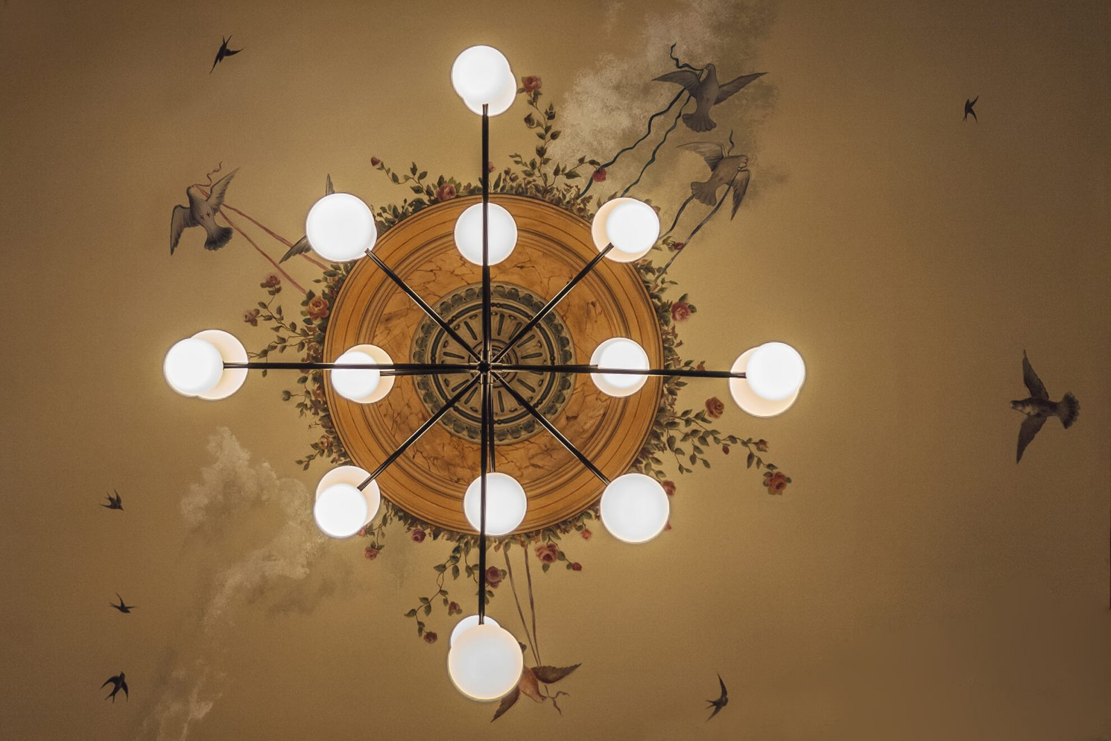 Detail of the ceiling painting with flowers and birds and a modern round bulb lamp