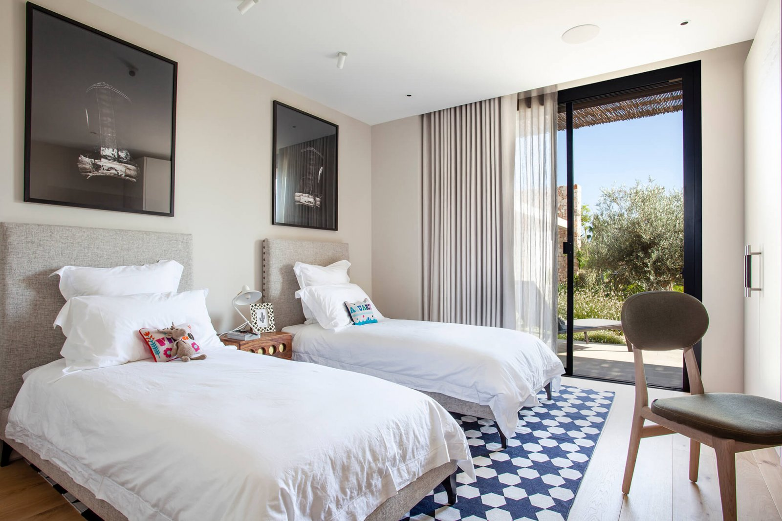 Detail view of a room, with two beds, built-in wardrobe and large glass doors to the garden of the Sol de Mallorca house