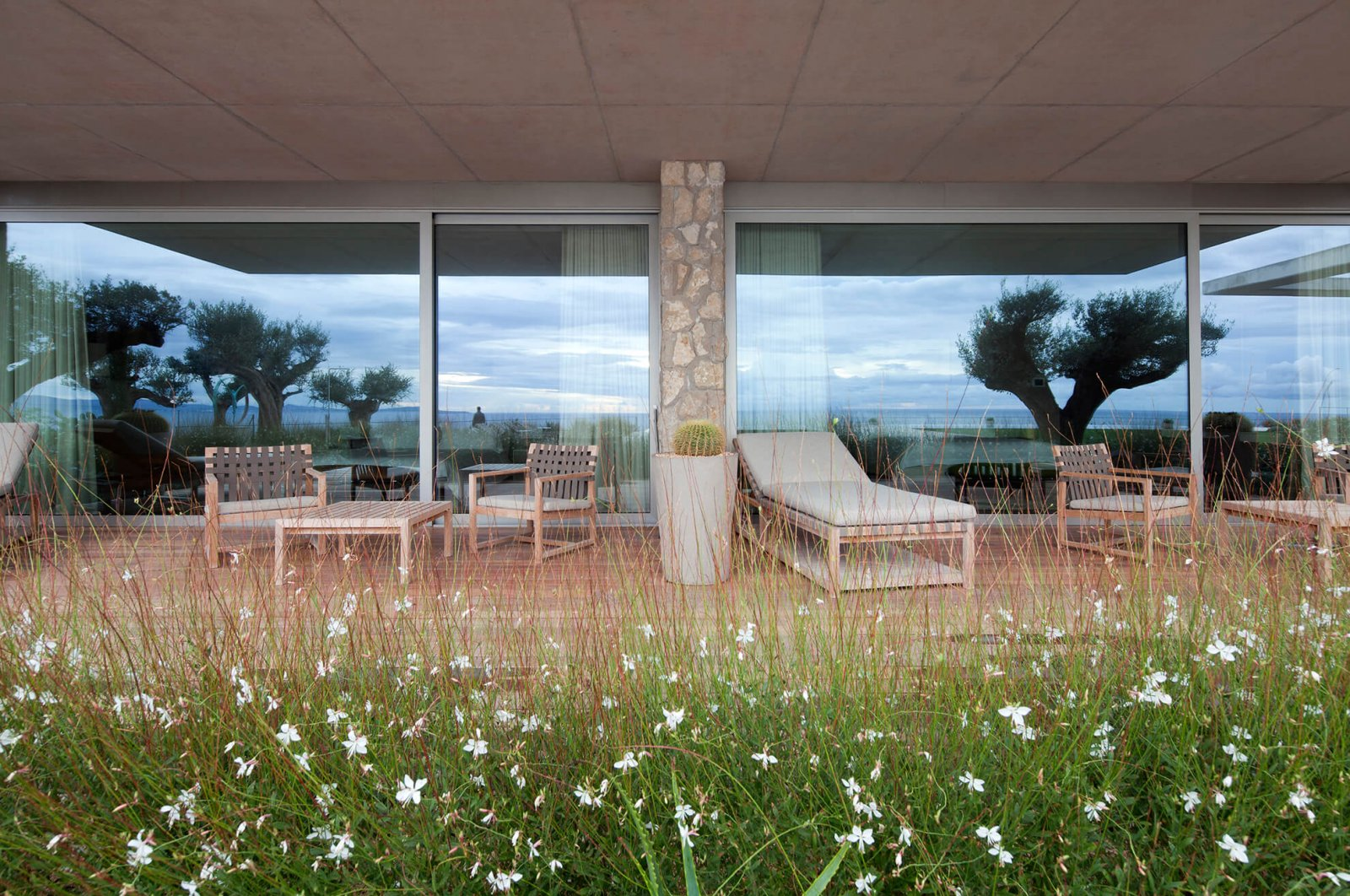 Detail view of one of the covered chill-out areas, in front of large glass doors and a garden area
