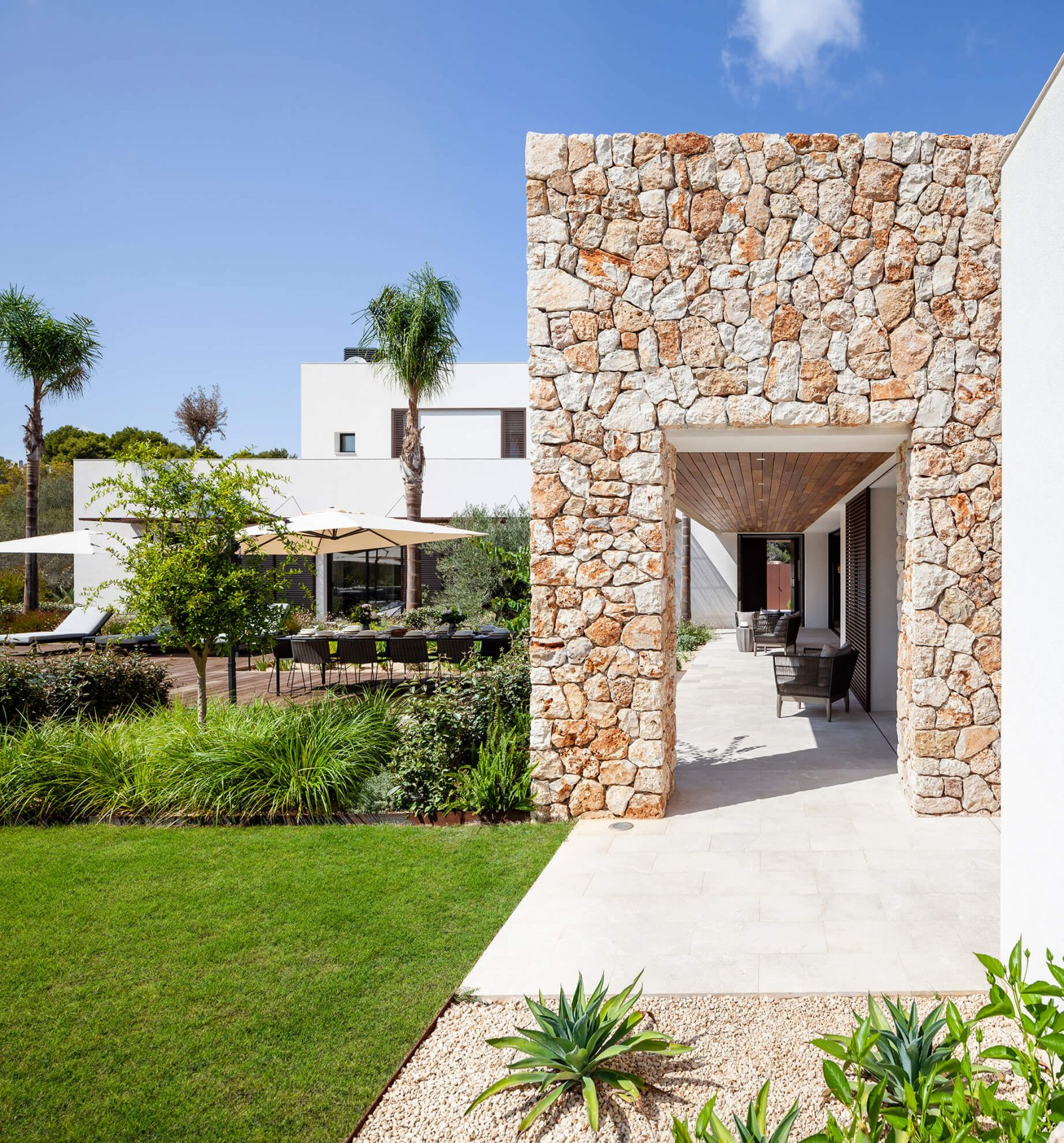Another view of the garden, chill-out and stone facade of the Sol de Mallorca house