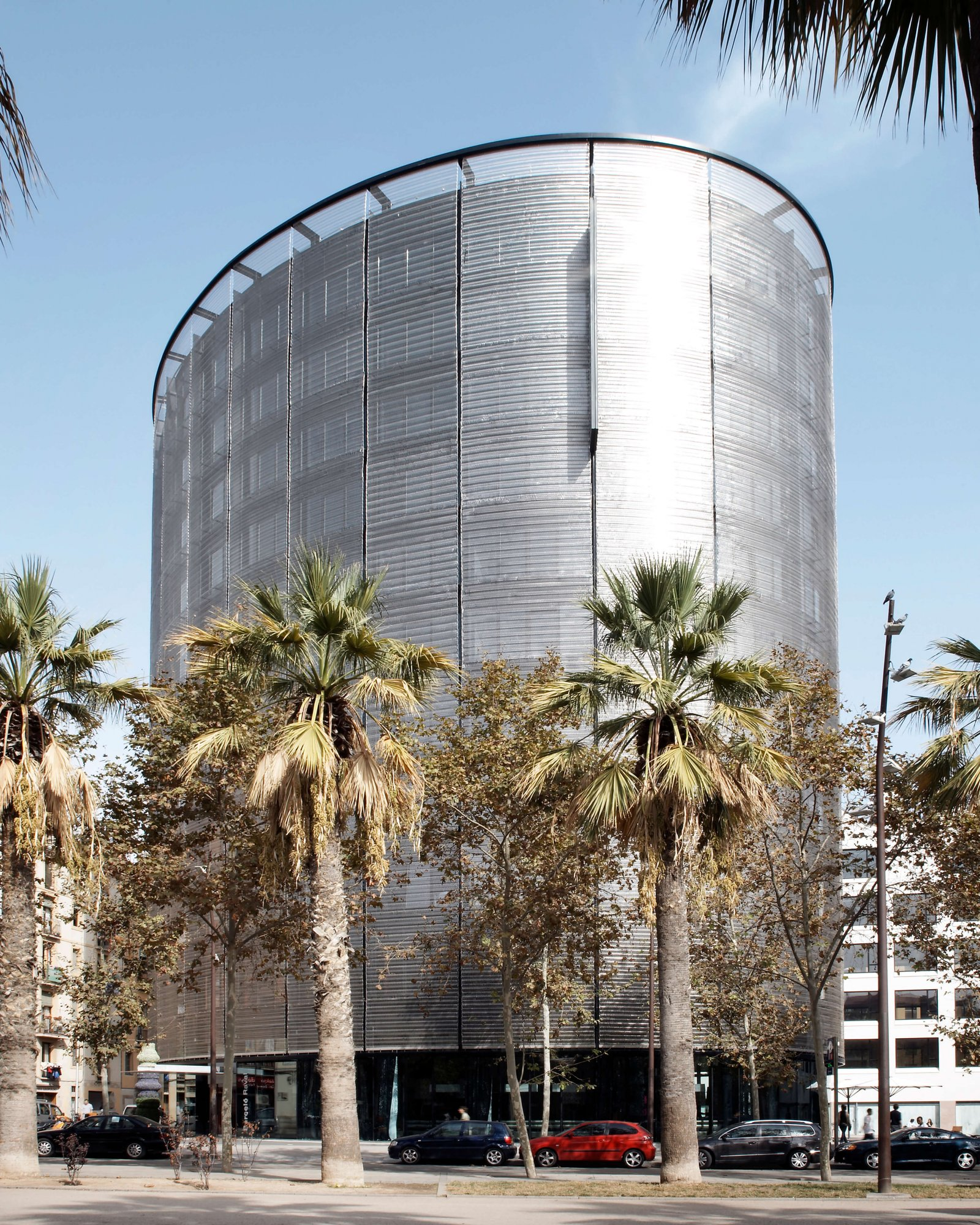 Another exterior view of the oval hotel raval tower with palm trees during the day