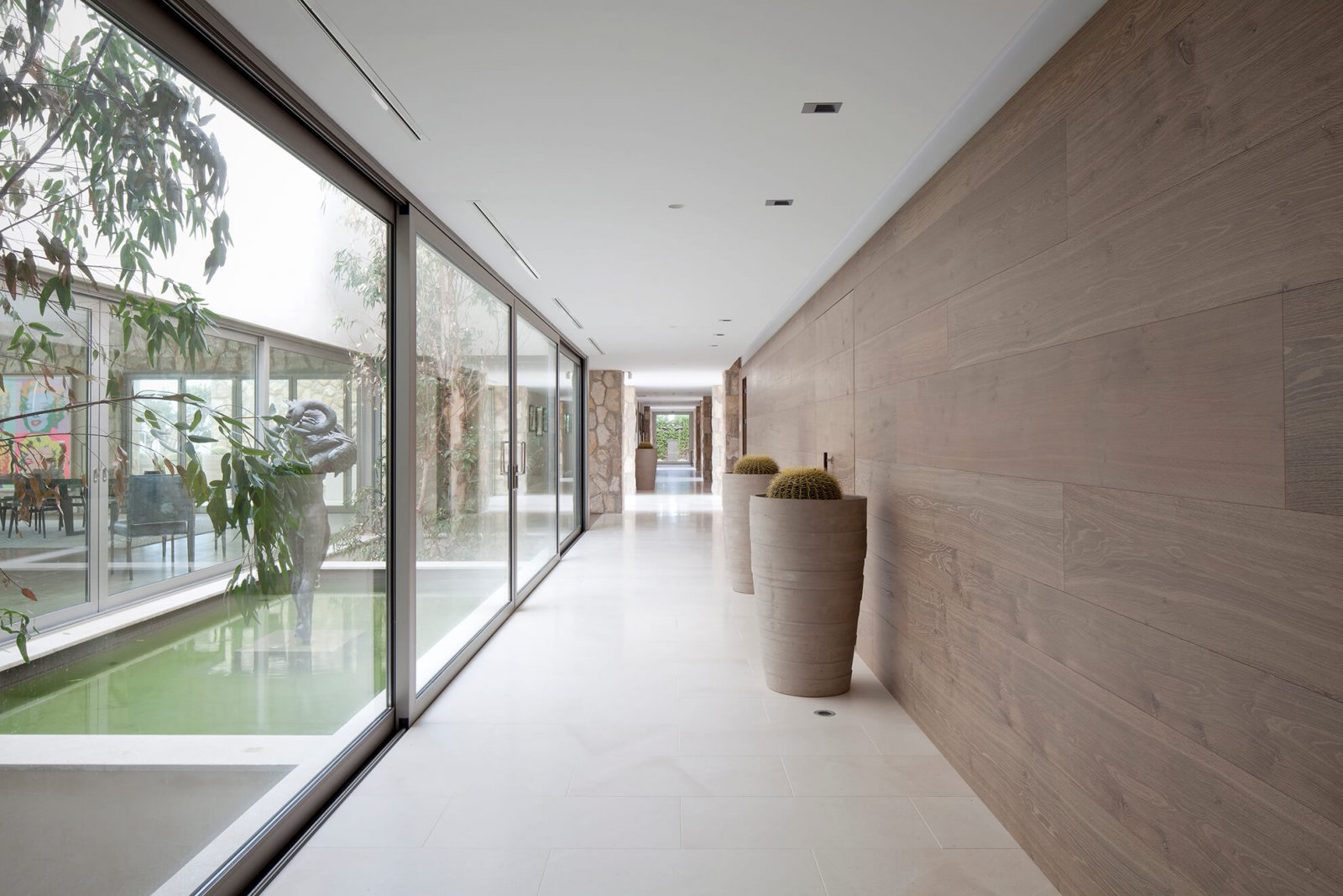 Detail view of one of the corridors of casa london, with sliding glass doors leading to an interior patio