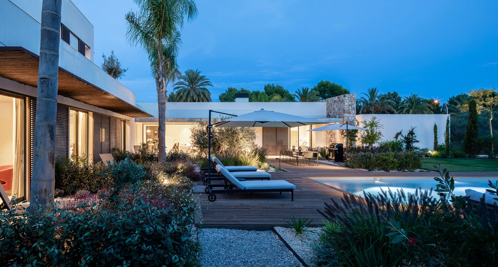 Side view of the garden with chill-out area and pool at night of the Sol de Mallorca house