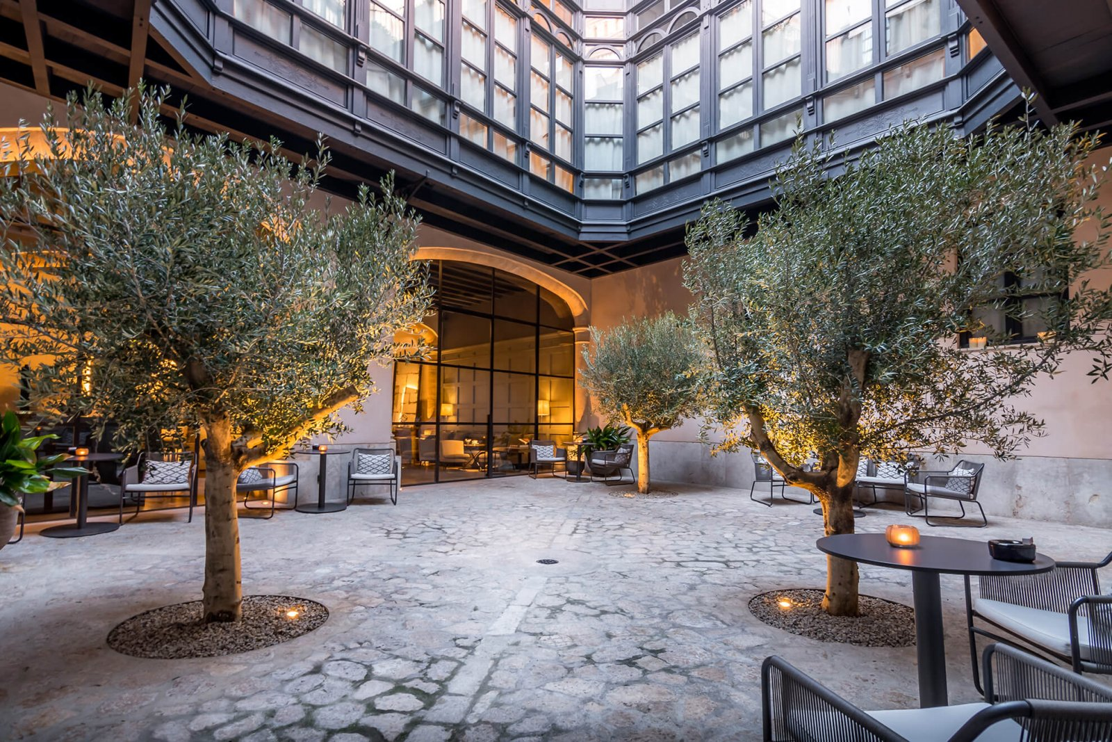 View of the interior patio with olive trees, stone floors and large windows with dark details